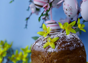 Easter background. On a blue background, branches of a blossoming apple tree decorated with pink Easter eggs. In the foreground is an Easter cake. Close-up, horizontal, cropped picture. Easter concept