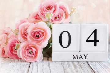 White wood calendar blocks with the date March 18th and pink ranunculus flowers over a wooden table. Selective focus with blurred background.