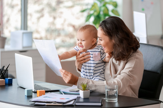 Working mother with her baby in office