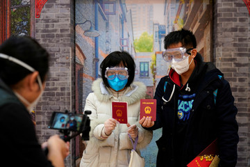 Jia, 29, and his wife Su, 28, poses with face masks and marriage certificates at a marriage registry office on Valentine's Day in Shanghai