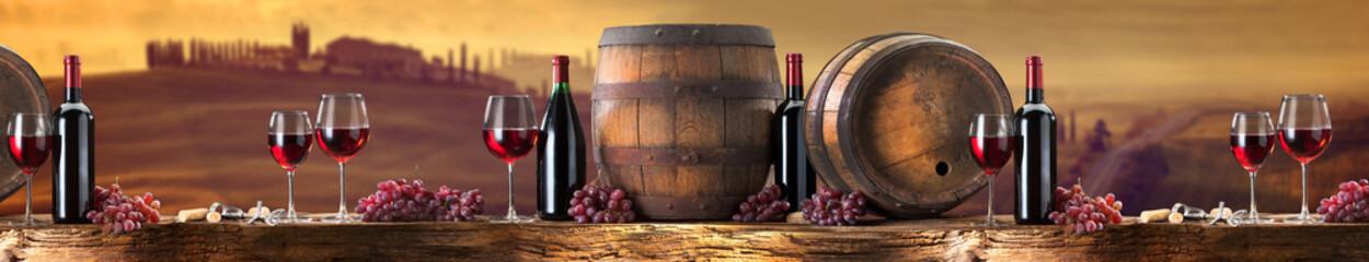Foto auf Gartenposter Dunkelbraun red wine on an old wood with a landscape background