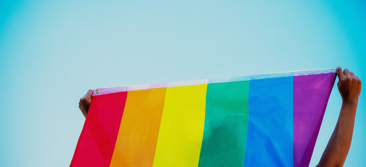 People holding and raising a rainbow flag over the blue sky