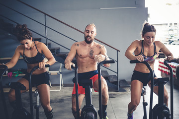 three people training indoor gym using stationary bike