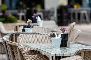 Close up shot of empty cafeteria or restaurant tables with chairs on street