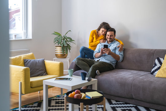 Couple using mobile phone at home stock photo. Positive couple is surfing internet on smart phone while sitting on sofa