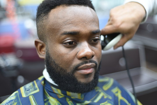 Black man in the Spanish barbershop. Cute black man makes a haircut in the African salon. Hair style. Haircut  for adults.