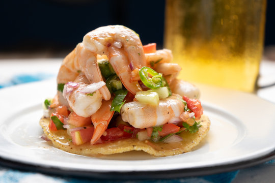 Mexican shrimp ceviche toast also called tostada on black background