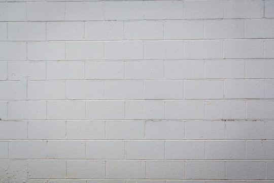 White painted cement concrete block wall with varying shades of white, off white and gray