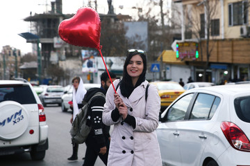 A young woman poses for a photo with a heart shaped balloon as a symbol of Valentine's day in Tehran