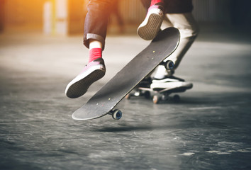 Jump of a teenager in jeans, pink socks and sneakers on a skateboard illuminated by a bright orange light.