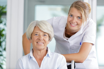 nurse supporting happy disabled senior woman in a wheelchair