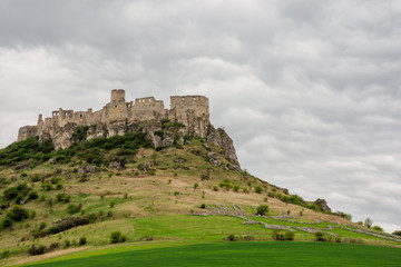ruins of spis castle on a cloudy day in springtime. famous travel destination of slovakia. UNESCO heritage. grassy meadow at the foot of the hill.