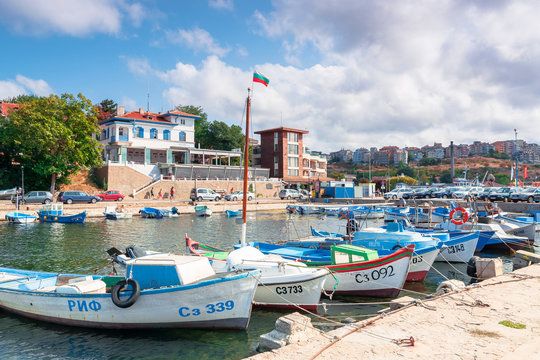 sozopol, bulgaria - SEP 09, 2019: fishing boats in port on a sunny day. town on the hill in the distance. bulgarian flag in the middle of a scene