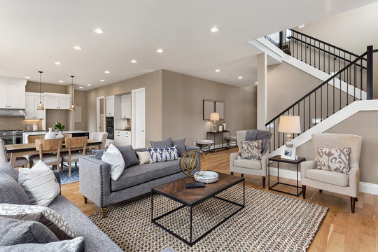 Living room and kitchen interior in new home with open concept floor plan. Kitchen features large island, hardwood floors, and stainless steel appliances. Living room is furnished