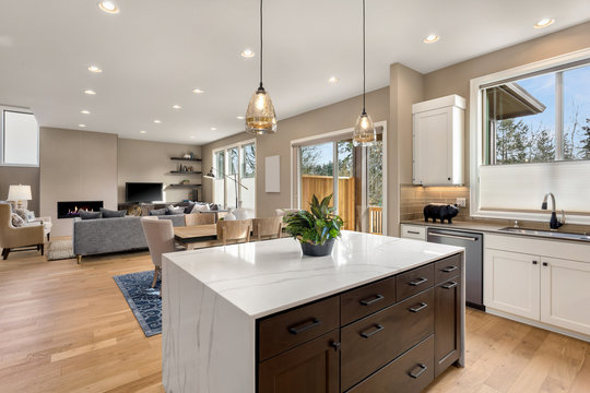 Kitchen and living room interior in new luxury home with open concept floor plan. Features island, hardwood floors, fireplace, dining area, and light filled spaces.