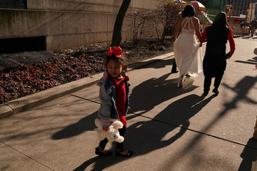 A little girl follows her parents who are getting married at the City Clerk's office on Valentine's Day in the Manhattan borough of New York City