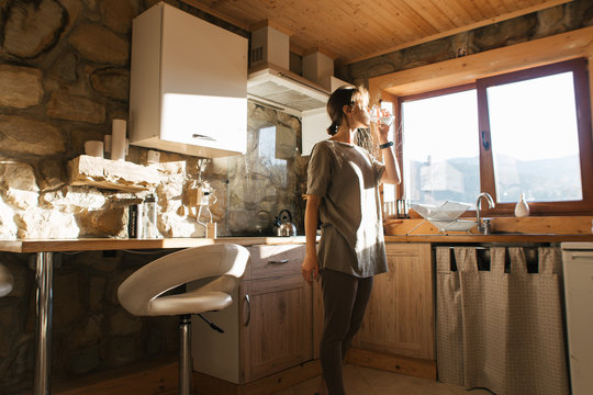 young woman drinking water in cozy kitchen in mountains