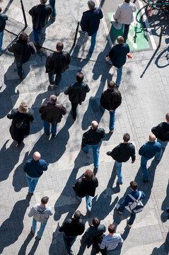 Overhead view of crowd of unrecognizable pedestrians walking on sidewalk