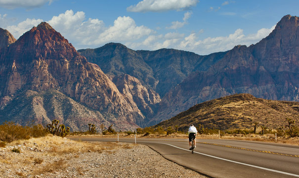 A lone cyclist peddling up a desert highway toward distance mountains