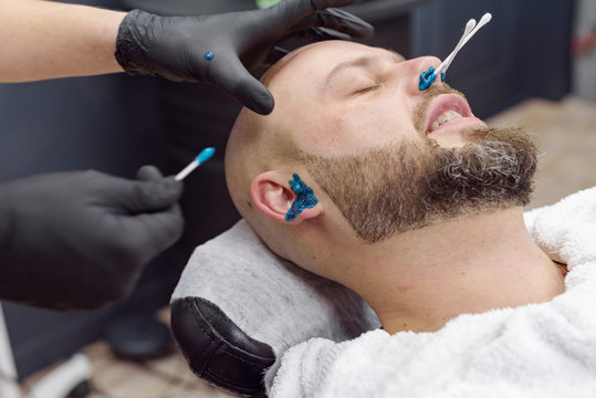 beard modeling in Barber shop, removing hair from the nose and ears with wax, male beauty and care concept