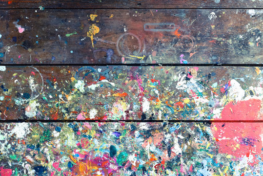 Artists workshop or studio bench covered with splattered paint built up in authentic texture on painted surface
