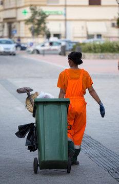 Garbage worker pulling trash can in street