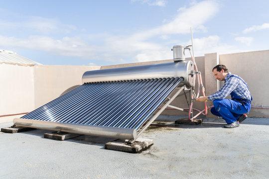 Male Plumber Repairing Solar Energy Boiler