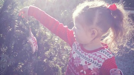 Wall Mural - Slow motion. Little girl in red dress on Christmas tree farm.