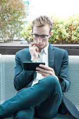 Serious pensive office worker watching content on cellphone. Young business man in eyeglasses and jacket sitting outside, looking at smartphone screen and touching chin. Watching video concept