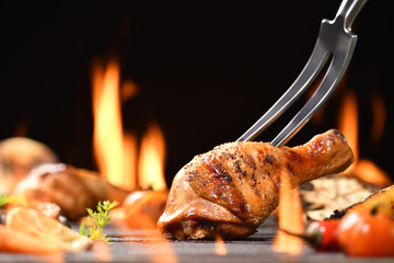 Wall Mural - Grilled chicken leg with various vegetables on the flaming grill