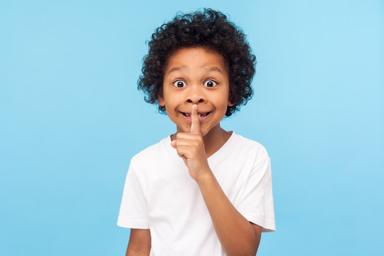 Shh, be quiet! Portrait of funny cute little boy with curly hair in T-shirt making silence gesture with finger on his lips, keeping some secret, child mystery. studio shot isolated on blue background