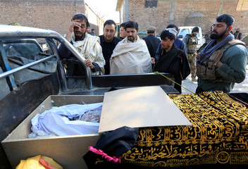 Relatives mourn next to the body of one of the victims of Friday's air strike in Surkhroad district of Nangarhar province, Afghanistan