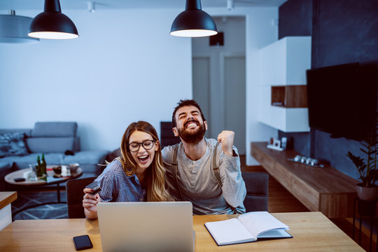 Young cheerful couple sitting at dining table and using laptop for online shopping. Man cheering for buying things that he want while woman holding credit card.
