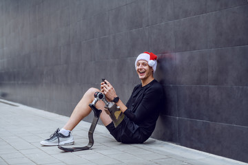 Fotomurales - Cheerful Caucasian sportsman with artificial leg and with santa hat on head sitting on ground, leaning on wall and sending wishes for christmas over his smart phone.
