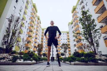 Fotomurales - Low angle view of handsome sportsman with artificial leg standing with hands on hips outdoors surrounded by buildings.
