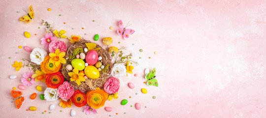 Creative holiday concept with easter eggs in nest, spring flowers and candy