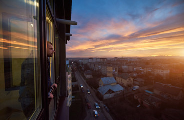 Adult man stands on the balcony and looks into the distance enjoying the sunset. Beautiful city landscape of a fiery sky at sunset. Roofs of houses and passing cars in the bustle of the city Wall mural