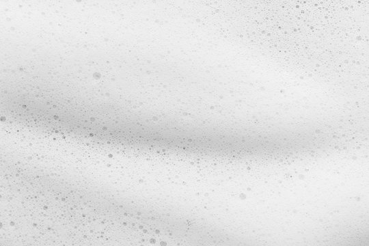 White cleanser foam texture background. Soap, shampoo bubbles closeup. Foamy skin care product sample
