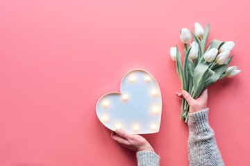 Springtime flat lay on pink, female woman hands holding bunch of white tulips, Spring flowers. Lightboard in heart shape in hands. Flat lay, top view, Mothers day or Valentine.