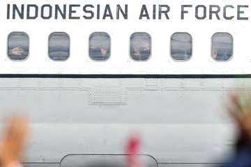 Indonesian citizens who were quarantined after being evacuated from Wuhan following the outbreak of the coronavirus, wave from Indonesian Air Force aircraft before they leave Natuna island at Raden Sadjad airbase in Riau islands