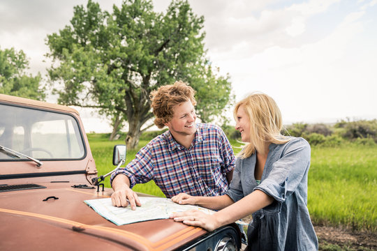 Young couple driving through the hills with an old jeep, reading a map. Bridger, Montana, USA