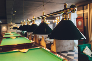 lamp over billiards green table balls and cues.