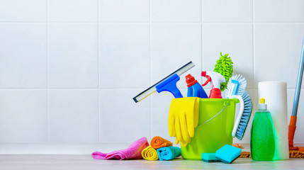 Bucket of cleaning supplies in the front of tiled wall