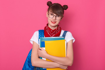 Horizontal shot of smiling lady student wears eyeglasses, red bandana over her neck, white casual t shirt, stands with folder in hands, happily looks directly at camera, poses on pink background.