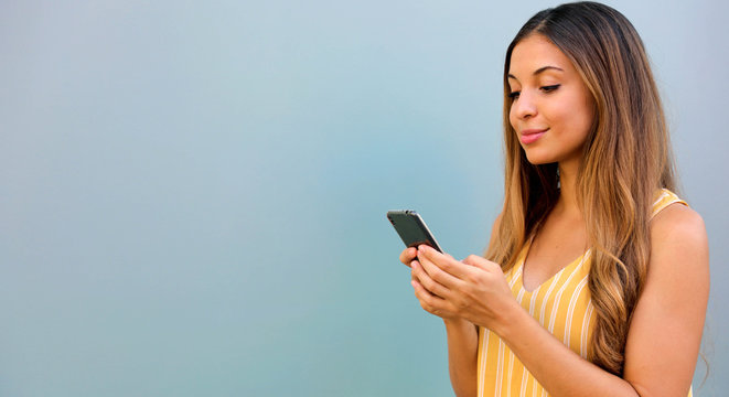 Brazilian woman typing on smart phone outdoor on gray background.