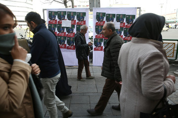 People walk past parliamentary election campaign posters in Tehran