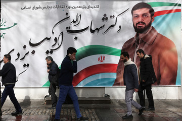 People walk past a parliamentary election campaign poster in Tehran