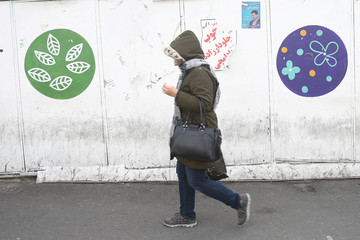 An Iranian woman walks past a parliamentary election campaign poster in Tehran