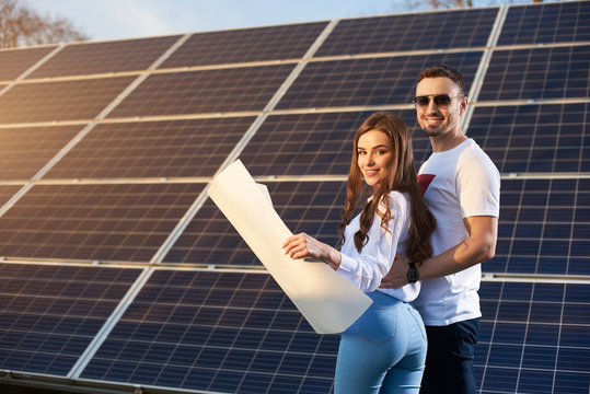 Young smiling sweet couple is standing by a solar module on a sunny day, looking at camera, holding a paper plan wearing similar clothes, copy space, side view