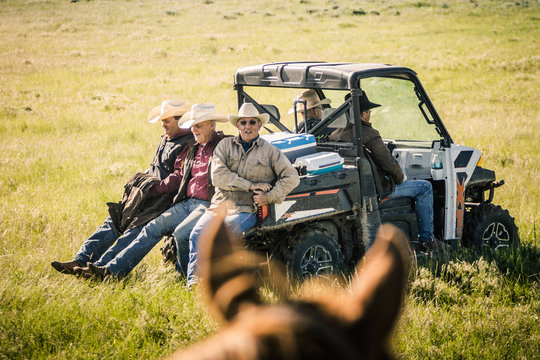 Cowboys riding across field on the back of an ATV. Cody, Wyoming, USA